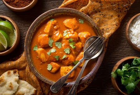 A bowl of delicious indian butter chicken curry with naan bread, basmati rice, and cilantro garnish.