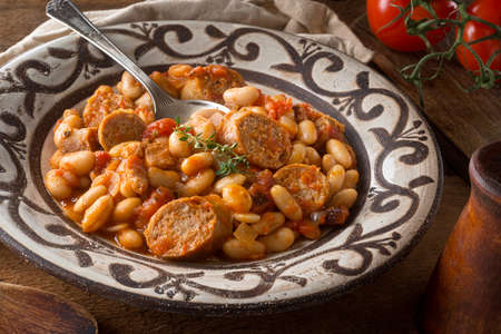 A delicious hearty cassoulet with artisanal sausage, tomato, bacon and white beans on a rustic tabletop. Stok Fotoğraf