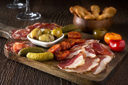 A delicious charcuterie assortment of meat, olives, gherkins, and pickled peppers with breadsticks on a wooden background. Archivio Fotografico