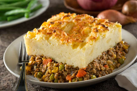 A serving of delicious homemade shepherds pie with ground meat, mashed potato, carrots, peas, corn, and cheddar cheese crust.