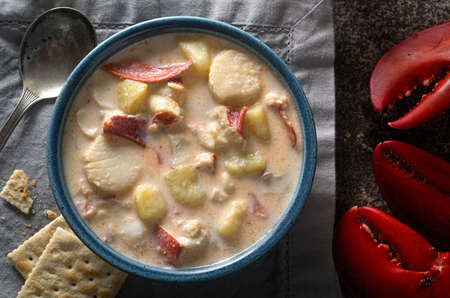 A bowl of delicious homemade seafood chowder with lobster, scallops, haddock, clams, and potato. Foto de archivo