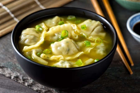 A bowl of delicious chinese wonton soup with green onion garnish. Stock Photo