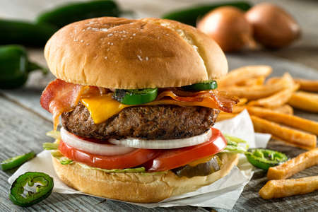 A delicious burger with bacon, cheddar, jalapeno pepper, tomato, onion, pickle and lettuce with french fries.