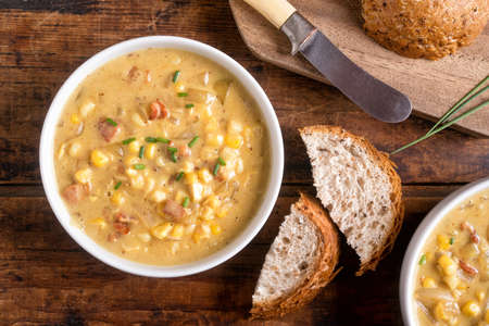 A bowl of delicious homemade bacon corn chowder with whole grain bread on a rustic wood table top. 版權商用圖片