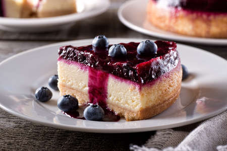 A slice of delicious blueberry cheesecake with fresh blueberries on a rustic wood table top. 스톡 콘텐츠