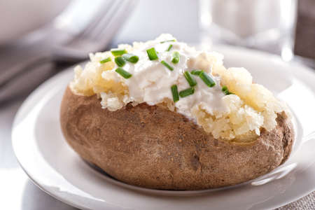 A delicious oven baked potato with sour cream and chives. Фото со стока