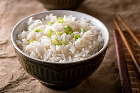 A bowl of delicious plain steamed rice with scallion garnish. 스톡 콘텐츠