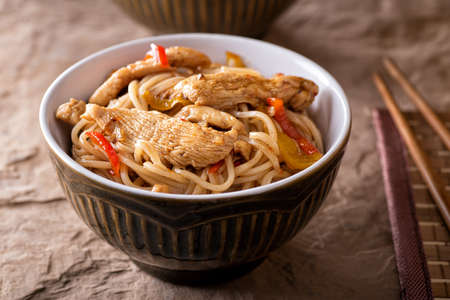 A bowl of delicious honey garlic noodles with chicken and peppers. 스톡 콘텐츠