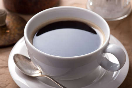 A cup of delicious fresh black coffee on a rustic table top. 스톡 콘텐츠