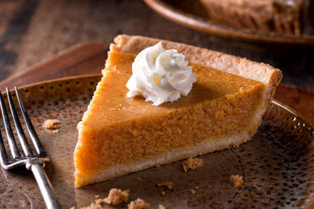 A slice of delicious home made pumpkin pie with whipped cream on a rustic table top. 스톡 콘텐츠
