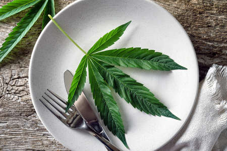 Conceptual image of a cannabis leaf on a plate with a knife and fork. 스톡 콘텐츠