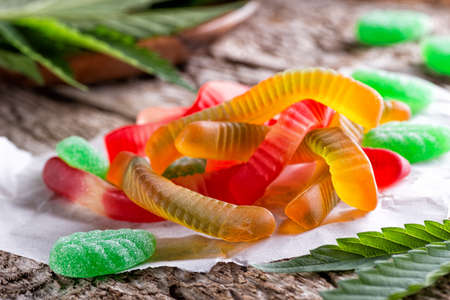 Cannabis infused gummy candy on a rustic table top with marijuana leaves. 스톡 콘텐츠