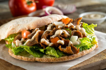 A delicious doner meat sandwich on pita bread with lettuce, tomato, onion and sauce. 스톡 콘텐츠