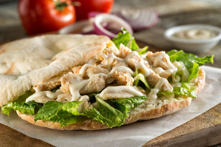 A delicious chicken pita sandwich with lettuce and sauce. 스톡 콘텐츠