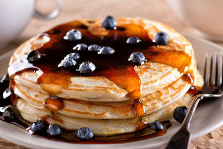 A plate of delicious blueberry pancakes with real maple syrup.