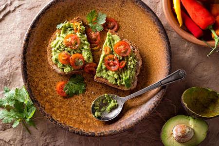 A slice of delicious avocado toast with sliced tomato and cilantro.