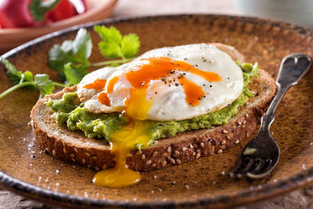 A slice of toast with delicious avocado, fried egg and hot sauce. 스톡 콘텐츠