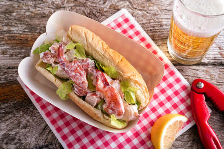 A delicious lobster roll with beer on a rustic wood table.