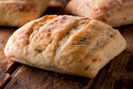 Fresh baked cheddar jalapeno ciabatta on a rustic wood board.