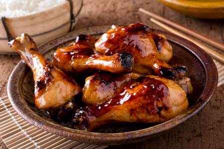 A bowl of delicious honey garlic chicken drumsticks with rice.