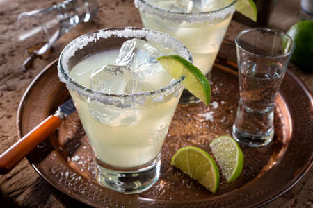 Delicious tequila and lime margaritas on a copper charger with coarse salt rimmer. 스톡 콘텐츠