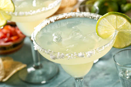 Delicious tequila and lime margaritas on an outdoor table with tortilla chips and pico de gallo.