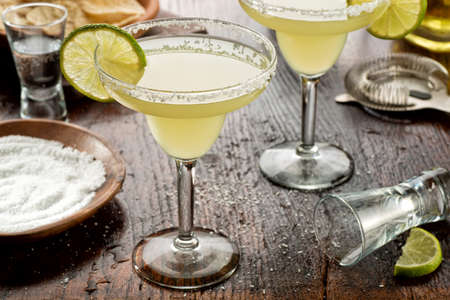 Delicious tequila and lime margaritas on a bar top with tortilla chips and pico de gallo. 스톡 콘텐츠