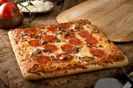 A delicious square crust flatbread pizza with pepperoni, bacon and mushrooms on a rustic wood table top.