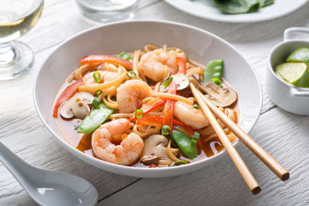 A bowl of delicious spicy asian shrimp noodle soup with mushroom, red pepper, snow peas and scallions.