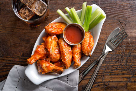 A serving of delicious spicy buffalo chicken wings on a pub style restaurant table top. 스톡 콘텐츠
