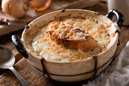 A bowl of delicious rustic french onion soup with toasted baguette and melted swiss cheese.