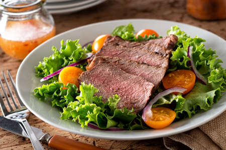 A delicious steak salad with leaf lettuce, red onion and yellow tomatoes.