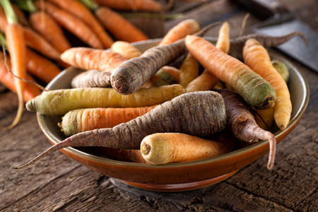 Raw fresh organic heirloom carrots in a bowl on a rustic harvest table. 스톡 콘텐츠