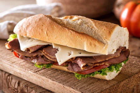 A delicious roast beef sandwich with swiss cheese, lettuce and tomato on a french bread baguette.