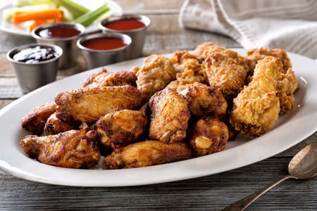 A platter of delicious mixed chicken wings with four dipping sauces.
