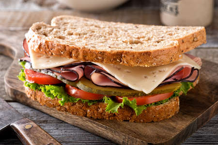 A delicious ham and cheese sandwich with lettuce, tomato and dill pickle on a rustic wood table.