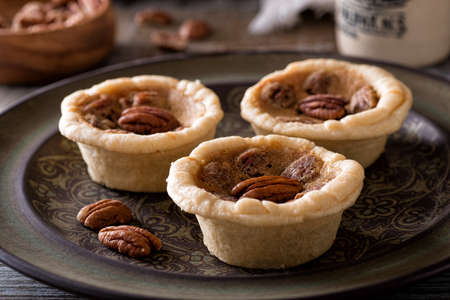 Delicious homemade mini pecan butter tarts on a rustic table top. 스톡 콘텐츠