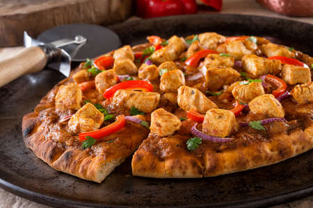 A delicious butter chicken pizza with red pepper, red onion and cilantro. 스톡 콘텐츠