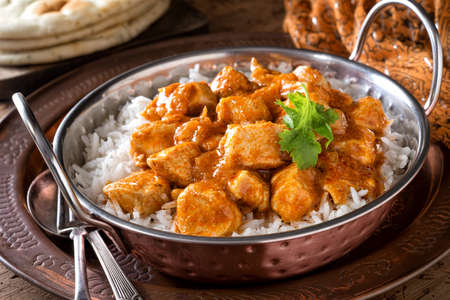 A bowl of delicious creamy butter chicken curry with basmati rice and garlic naan bread. 스톡 콘텐츠