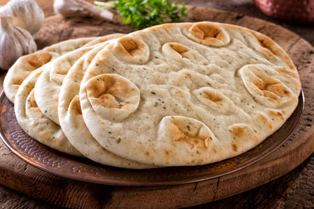Fresh garlic cilantro naan bread on a copper plate with rustic wood background.