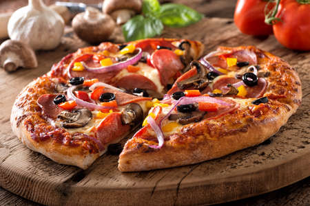 A rustic homemade pepperoni pizza with mushrooms, peppers, red onion and black olives on a rustic board. 스톡 콘텐츠