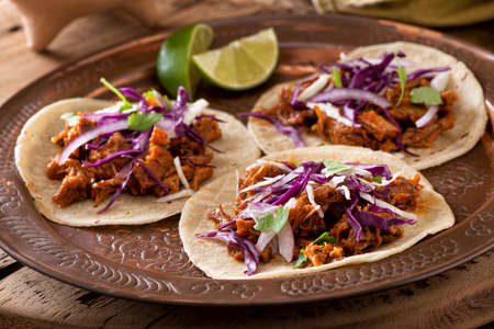 Three delicious pulled pork tacos with cabbage, onion and cilantro.