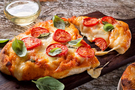 A delicious rustic homemade pizza margherita with fresh mozzarella cheese, roma tomatoes and basil. 스톡 콘텐츠