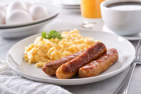 A plate of delicious scrambled eggs and breakfast sausage with coffee and orange juice. Фото со стока