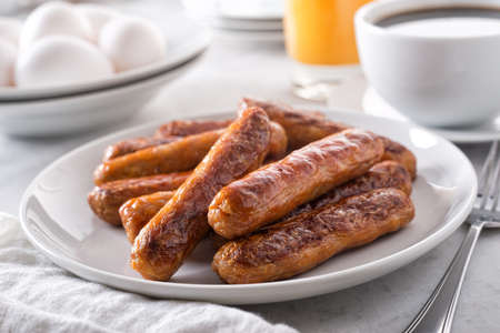 A plate of delicious cooked breakfast sausage with coffee, orange juice and eggs.