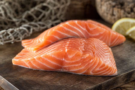 Fresh raw salmon fillets on a wooden board with lemon and fish net background.
