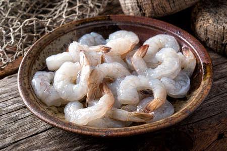 Un bol de crevettes blanches du Pacifique crues fraîches décortiquées avec la queue.