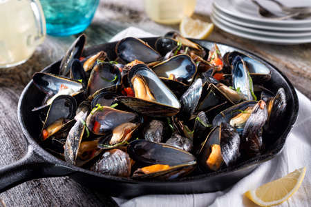 Delicious fresh steamed mussels on a rustic wood table top.