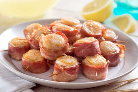A plate of delicious bacon wrapped scallops with lemon. 스톡 콘텐츠