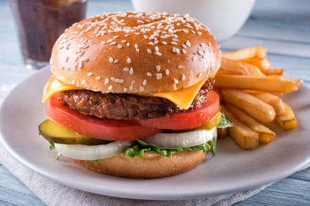 Una deliciosa hamburguesa con queso sin carne a base de plantas con lechuga, cebolla, pepinillos, tomate y papas fritas.